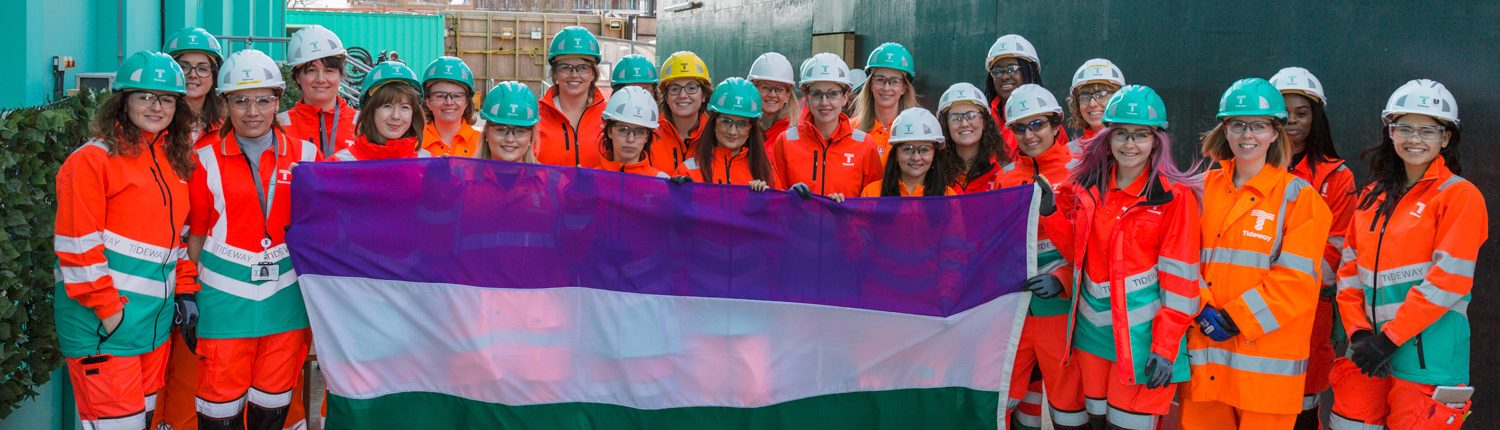 Women Crossrail workers on site holding suffragette flag