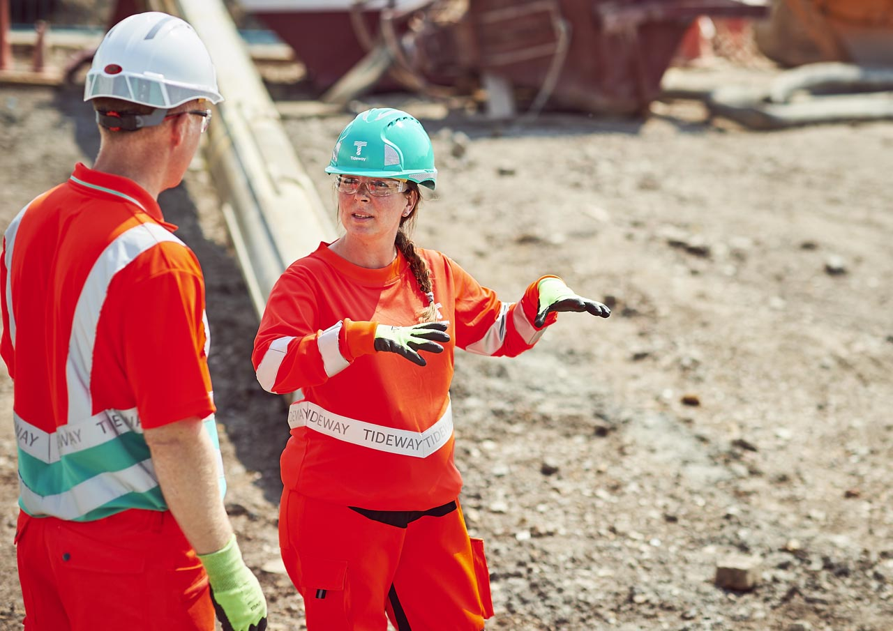 Women instructs male colleague on building site