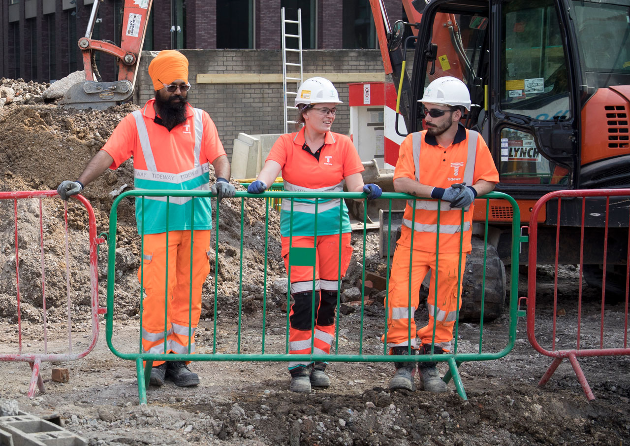 Women worker on construction site with two male colleagues