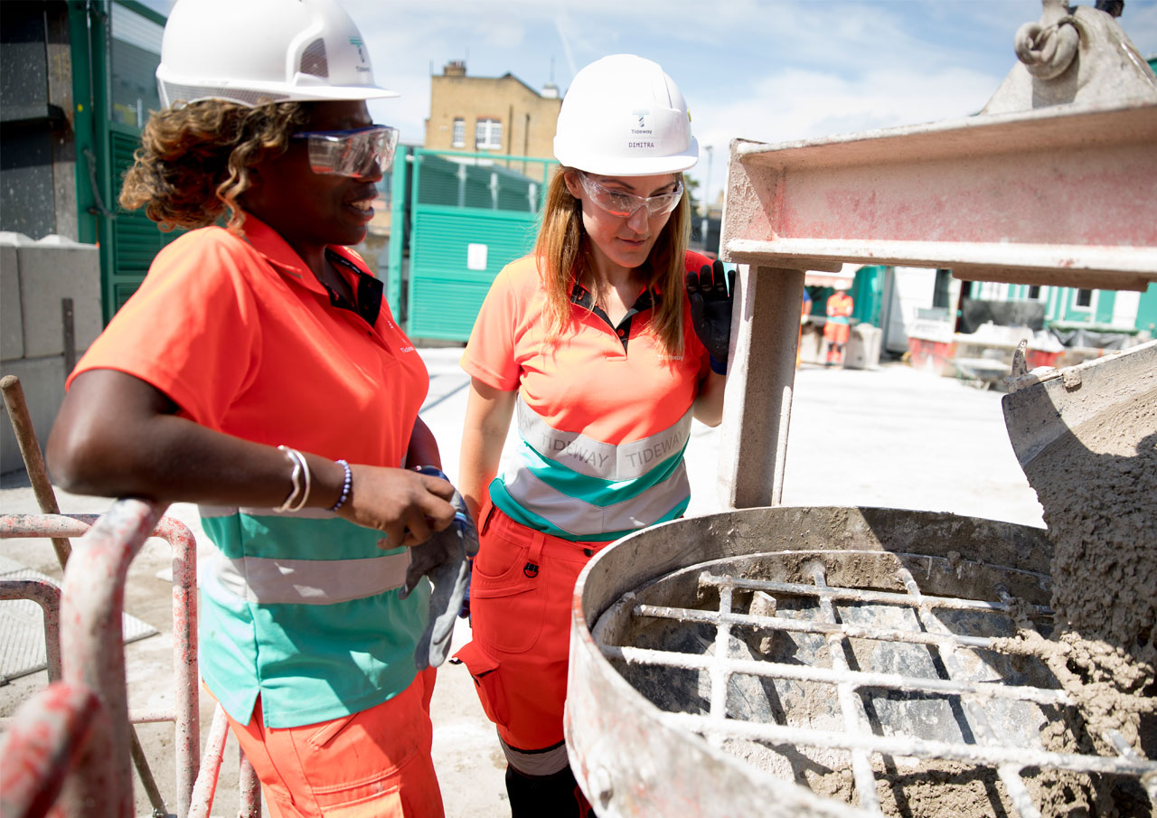Two women working cement mixer on construction site